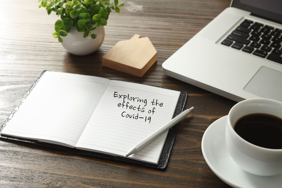 Image of desk with laptop, coffee, and a notepad reading 'Exploring the effects of Covid-19'